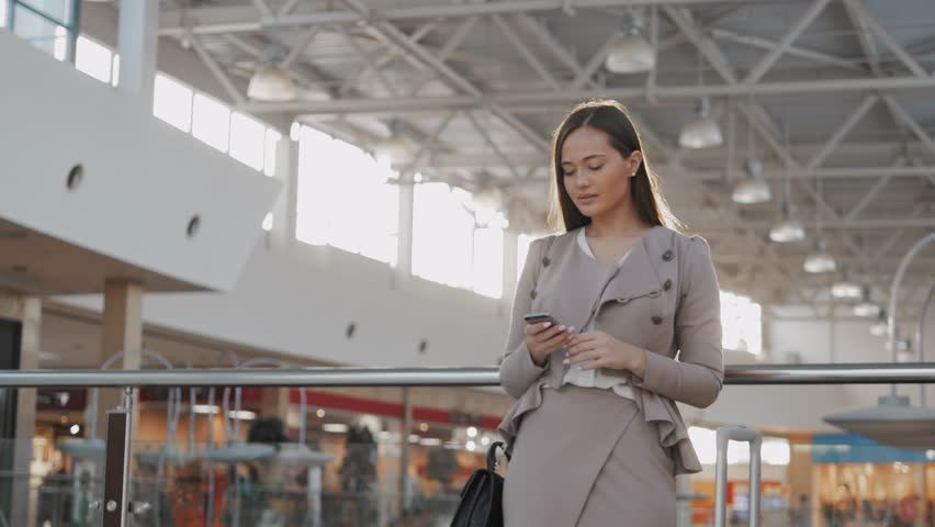 Happy young woman using smart phone in shopping mall. Businesswoman freelancer with smartphone in airport terminal. | Shutterstock HD Video #21536551