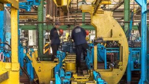 Tractor engine assembled on the factory production line on tractor factory timelapse. Workers in uniform install gear parts