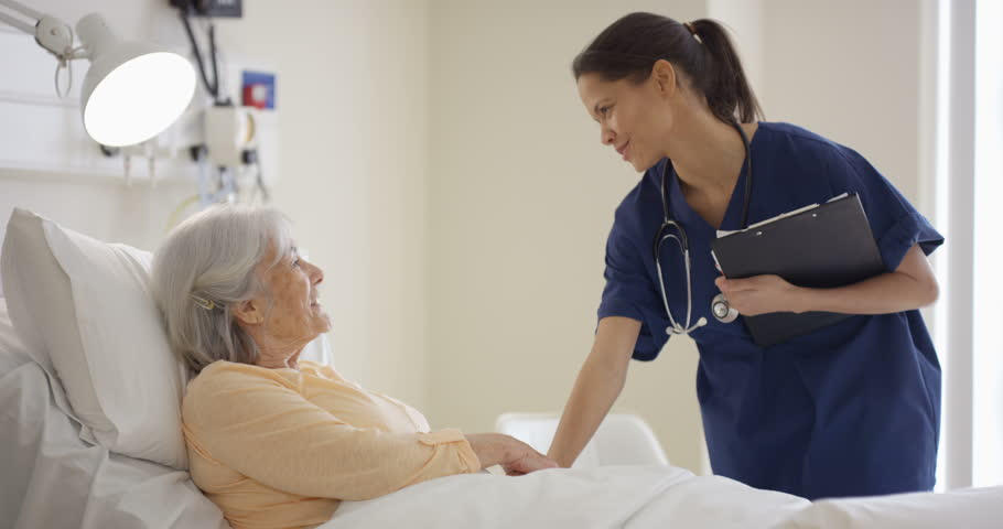 4K Caring medical worker in hospital talking to elderly lady at her bedside (UK-Oct 2016) #21577141