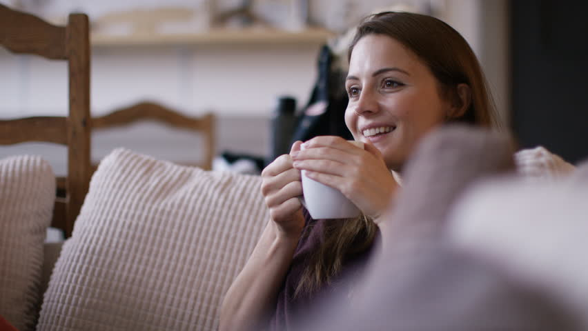 4K Attractive woman at home relaxing with a hot drink and tv