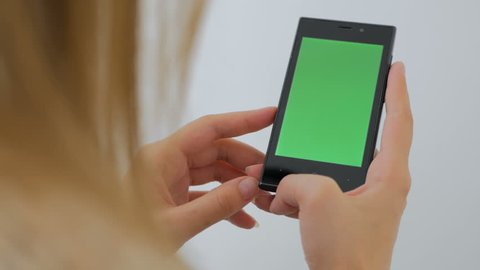 Woman using vertical smartphone with green screen. Close up shot of woman's hands with mobile Close up shot of woman's hands with mobile. White background
