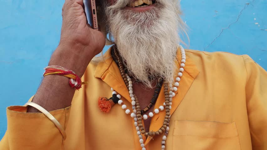 Tilt up closeup of a bearded Hindu priest wearing traditional saffron clothes on a call in Pushkar, Rajasthan