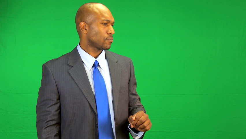 African American businessman in front of a green screen making hand gestures in a virtual business environment