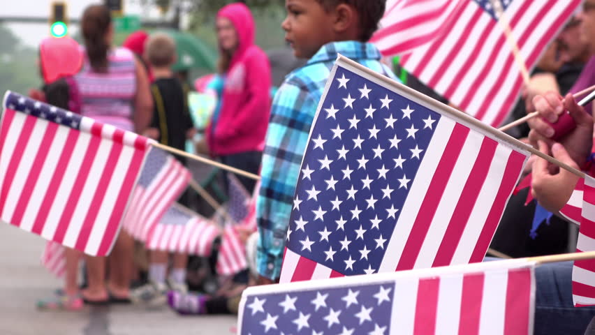 FAIRBORN, OH - JULY 4: People holding American flags along parade for holiday of United States Independence on July 4, 2016 in Fairborn, Ohio.