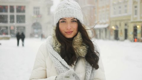 Street emotional portrait of young beautiful woman in city Model looking at camera. Lady wearing stylish classic winter knitted clothes. Snowfall