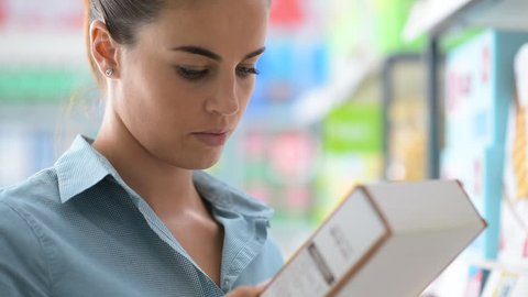 Woman doing grocery shopping at the supermarket, she is reading a product label and nutrition facts on a box