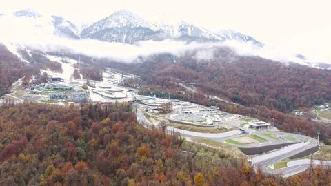 Aerial View. Flying over the city in the mountains. Bobsled track in Sochi.  Sochi Krasnaya Polyana Aibga. Aerial drone shot. 4K 30fps