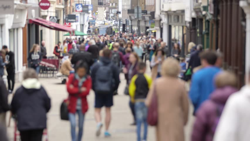 A defocussed shot of anonymous people walking on a busy British high street