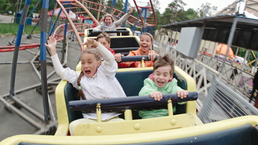 Happy kids yelling, raising arms and waving while riding roller coaster in amusement park