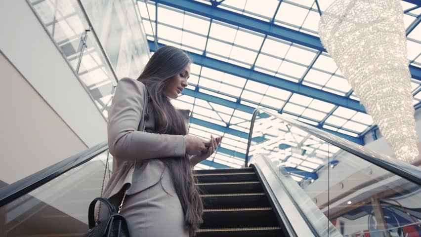 Confident woman is reading e-mail in internet via mobile phone, while is standing in shopping center on escalator. Female is booking on-line car, while is standing in airport near moving staircase