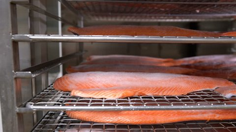 Many pieces of salmon fillet on the shelves ready for smoking.