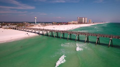 Fishing pier extends off white sandy beach into the Gulf of Mexico