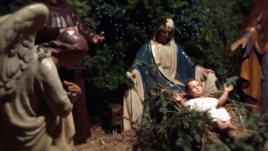 Christmas nativity scene with Mary, Joseph, and the Angel Gabriel looking down on baby Jesus in his manger