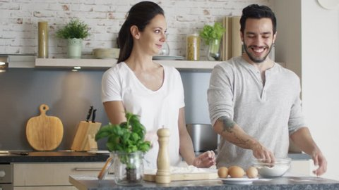 Happy Young Couple Cooks in the Kitchet. As a Joke They Started Throwing Flour at Each Other. Then Smilingly Embrace. Shot on RED Cinema Camera in 4K (UHD).