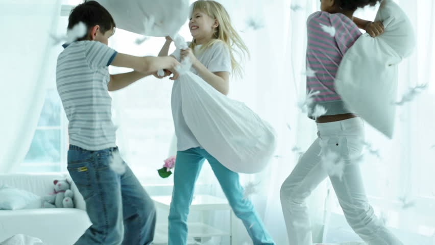 Kids pillow fighting so hard that feathers are falling all around them