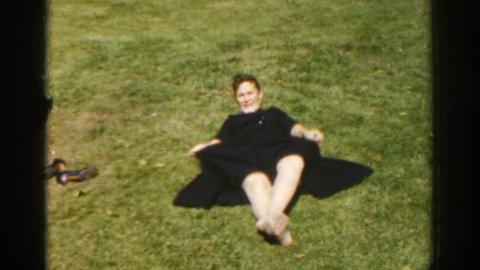 IRELAND 1961: a woman in a dress doing situps in a field of grass