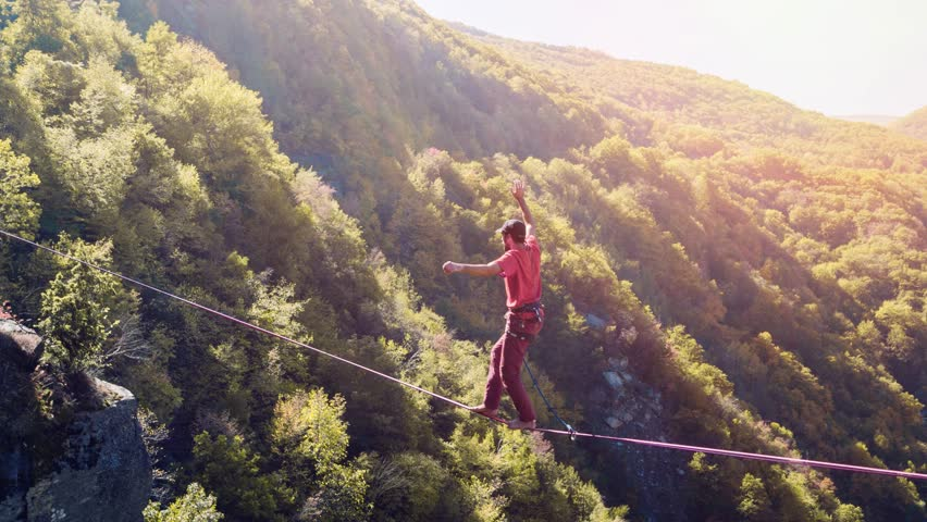Drone Footage Of Man Balancing On Tightrope Above Mountains Walking Extreme Sport Danger Leisure Adventure Brave Slacklining Fear Sunny