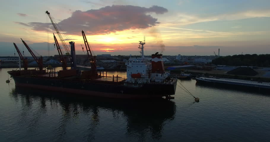 Anchored Cargo ship in a harbor unloading cargo with a large moving crane with a beautiful sunset in the background (cargo transhipment). Aerial Ultra HD view while rotating round the ship.