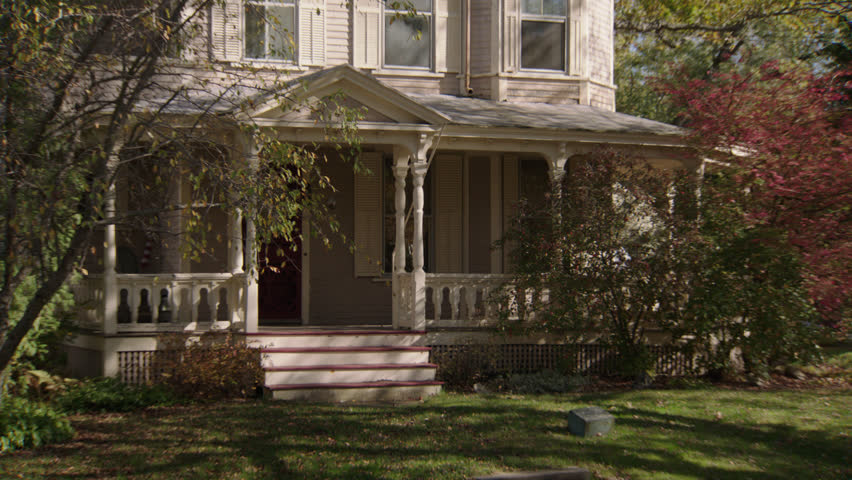 Day tight front beige wood clapboard house , wrap around porch, bay windows, turret, autumn, fall trees (Oct 2012)