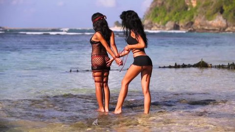 Two young glamorous sexy beautiful brunettes with shibari posing and playing on the beach. Tied blindfolded submissive girl and dominant girl. Geger beach. Bali, Indonesia
