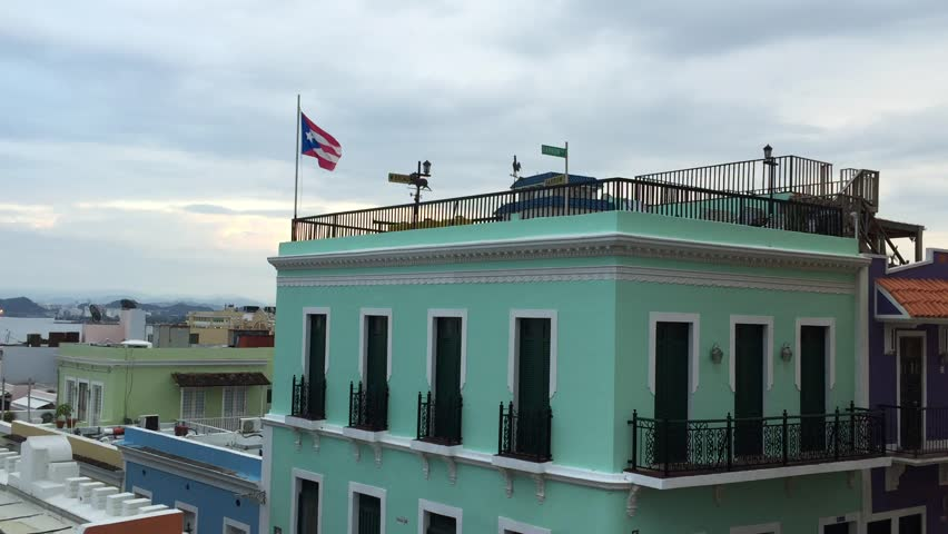 June 2015, Puerto Rico: The Puerto Rican flag hangs on top of a building in Old San Juan. The flag represents and symbolizes the island and its people. The origin of the flag can be traced to 1868.