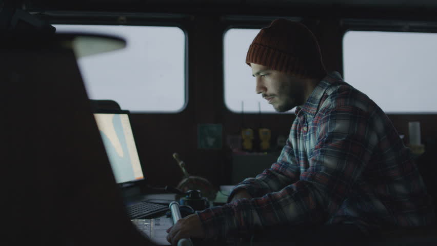 Captain Surrounded by Monitors and Screens with Sea Maps Pilots Commercial Fishing Ship. Shot on RED Cinema Camera in 4K (UHD).