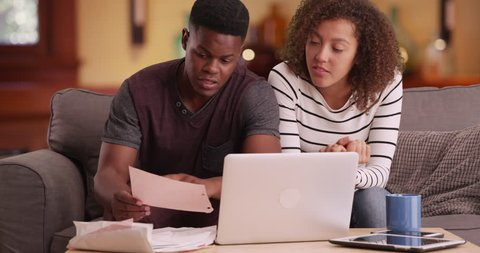 African American couple pays their bills on their laptop. Black millennial man and woman does their taxes online using computer. 4k.