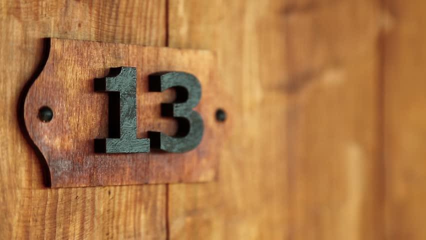 Hotel room number thirteen. Wooden door of room 13. Triskaidekaphobia - superstitious fear of number thirteen