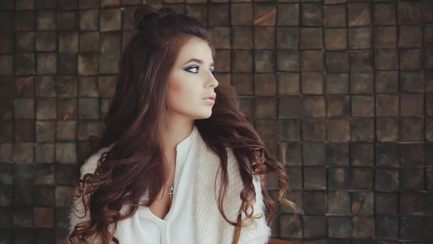 Portrait of pretty wistful brunette woman with bright smokey eyes make-up on the wooden background | Shutterstock HD Video #21855220