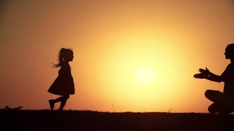 little girl with mom,the concept of family happiness,the sunset slow motion silhouette