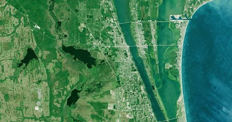 High-altitude overflight aerial of Kennedy Flight Center and adjacent coastland. Clip loops and is reversible. Elements of this image furnished by NASA