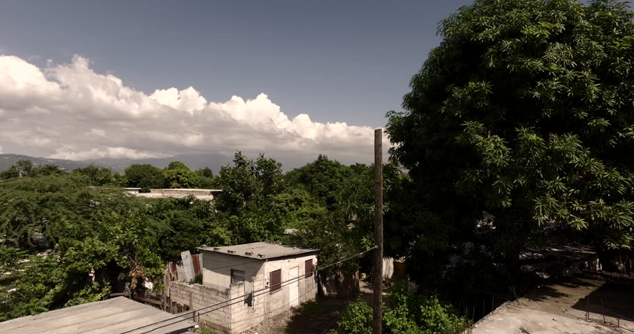 Low altitude aerial flying through a town in Jamaica.