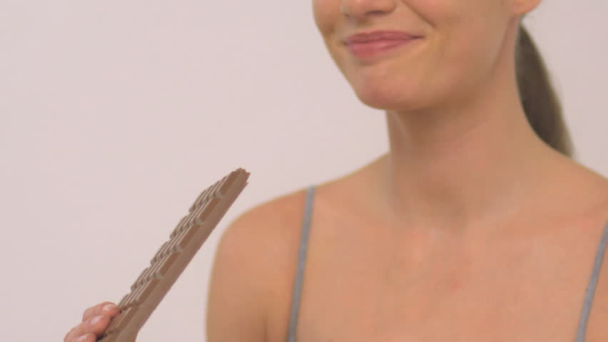 MEDIUM CLOSE UP OF A WOMAN EATING CHOCOLATE ON WHITE BACKGROUND