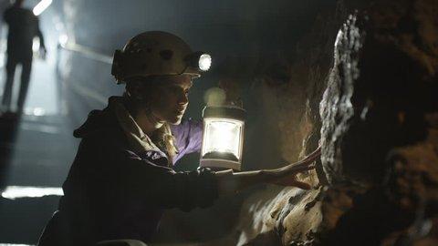 4K Potholers exploring cave system, shafts of light penetrating the dark (UK-Oct 2016)