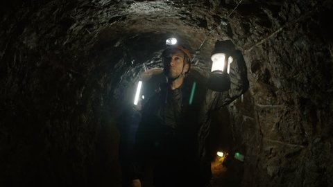4K Team of potholers with hard hats and lamps exploring underground cave system. (UK-Oct 2016)