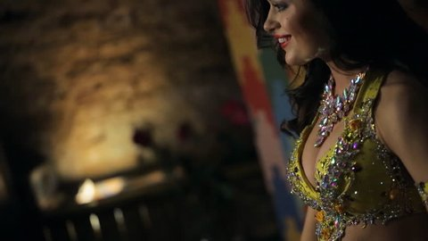 Beautifull caucasian woman in costume for belly-dance dancing indoors