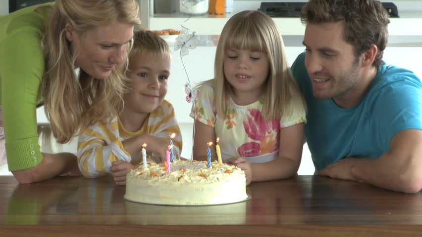 MEDIUM SHOT OF A GIRL BLOWING OUT CANDLES ON A BIRTHDAY CAKE