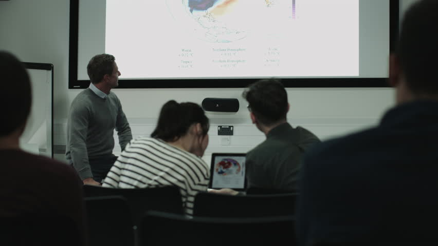 Professor teaching with projector synced to students' digital tablets | Shutterstock HD Video #21951661