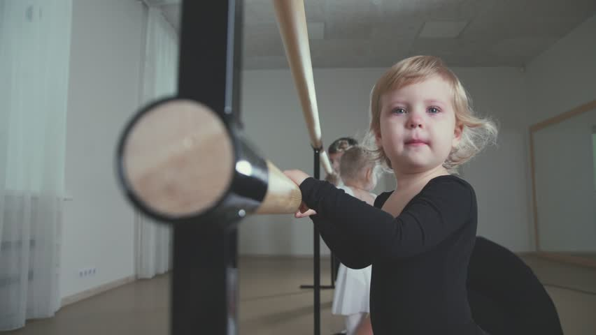 Sad girl about ballet bar. Cute little girl with sad eyes crying in the dance school. Portrait of a little upset girl ballerina. Little ballerina practicing ballet dance at barre in the studio