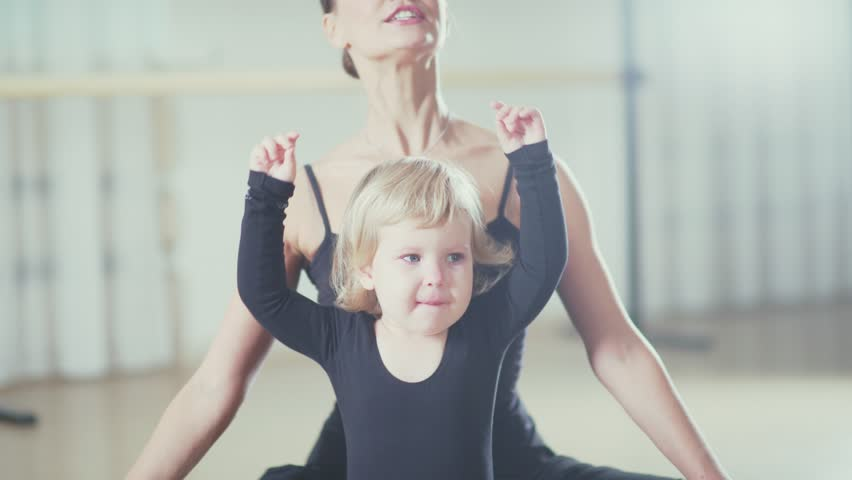 Little sad girl and a strict teacher in the dance school doing stretching. A teacher at the ballet school helps the little girl to do stretching and corrects its motion. Children's ballet school