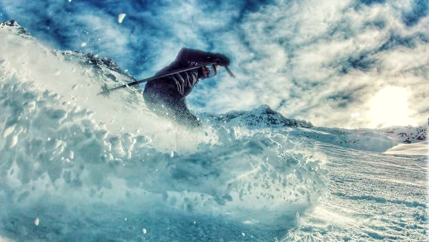 Skier on a sunny day, frozen in motion with moving snow powder and clouds, captured in high dynamic range footage.