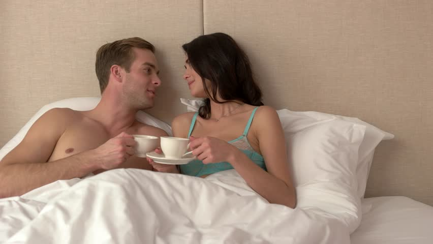 Perfect Couple Holding Cups In Bed. Man Smiling And Kissing Woman. You Are My Joy