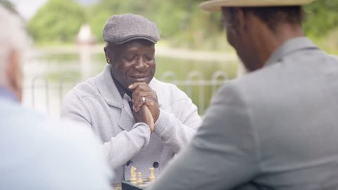 4K Portrait smiling senior man playing chess in the park with a friend (UK-Oct 2016)