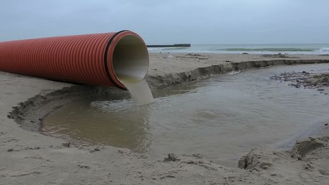 An orange plastic storm drain pipe with storm water runoff flowing to the sea. Video about waste water resources. Sewage pollutes the ocean.
