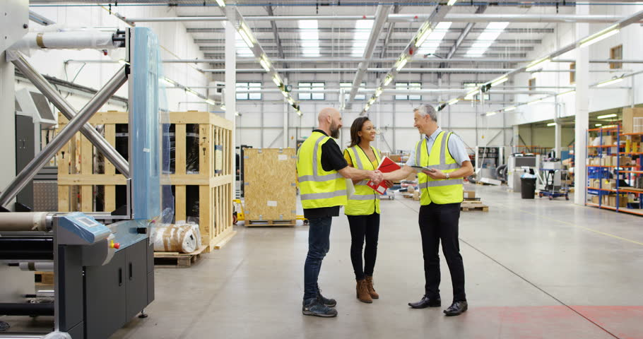 4K Management team having a discussion in factory warehouse, with workers busy in the background. Slow motion. | Shutterstock HD Video #22019371