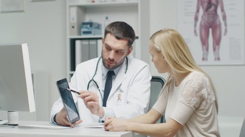 Doctor Shows to His Woman Patient Tablet Computer with X-Ray on it.