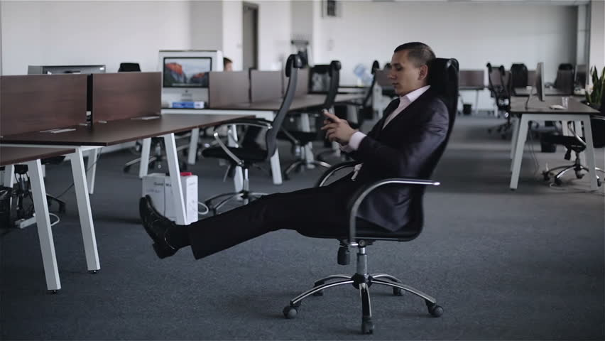 A young businessman with mobile phone in hands is turning around sitting in armchair in the big office. Rotating  motion of the man in classic suit.