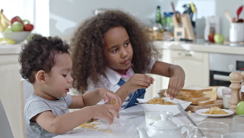Little brother and sister eating dinner together: boy dropping milk and spaghetti on table and mom taking care of him