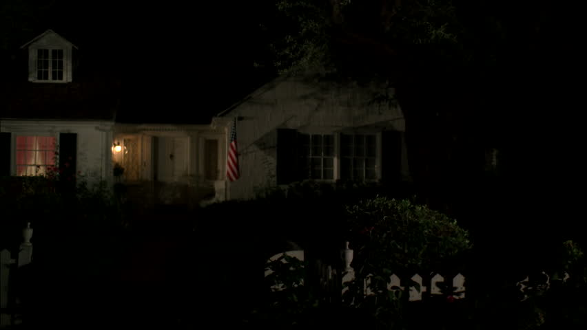 Night Pan Left Two Story House Cottage With Wood Shingle Roof Black Shutters White Picket Fence American Flag Only 1st Floor Lit Stock Footage Video