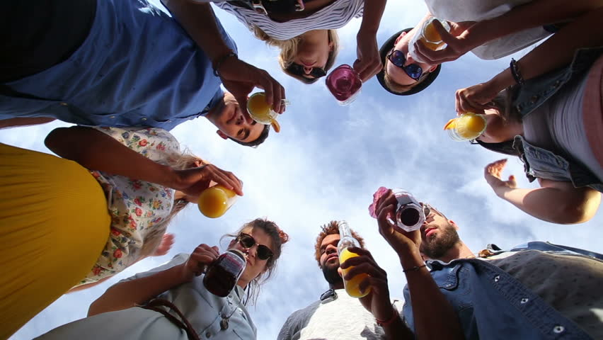 Group of eight young happy friends looking down at camera and toasting with cocktails